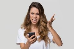 Annoyed angry woman mad about stuck phone isolated on background. Annoyed angry young woman mad about spam message stuck phone looking at smartphone isolated on stock image
