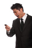 Annoyed Asian Man yelling at his phone. Isolated on white Royalty Free Stock Photos