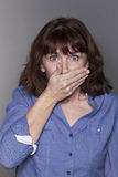 Annoyed attractive mature woman hiding her mouth Stock Photos