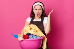 Annoyed beautiful woman raises hand with anger, feels fed up of washing clothes, being overworked, exclaims in dissatisfaction,. Dressed casually, isolated over stock photo