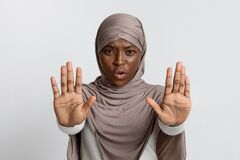 Annoyed Black Lady In Hijab Making Refuse Stop Gesture With Opened Palms