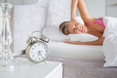 Annoyed blonde covering her ears from the alarm clock noise Royalty Free Stock Images