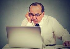 Annoyed bohrte den Mann, der wie man Computer lernt, benutzt Stockbilder