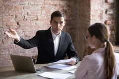Annoyed boss points employee at door because of document error. stock photos
