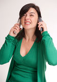 Annoyed brunette talking with two phones Royalty Free Stock Image