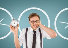 Annoyed business man holding a clock against background with clocks. Digital composite of Annoyed business man holding a clock against background with clocks Royalty Free Stock Photos