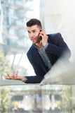 Annoyed business man talking on mobile phone Stock Image