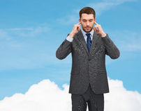 Annoyed businessman covering ears with his hands Royalty Free Stock Images