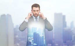 Annoyed businessman covering ears with his hands Royalty Free Stock Photo