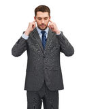 Annoyed businessman covering ears with his hands Stock Photos