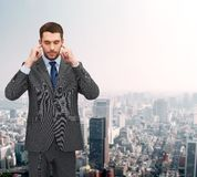 Annoyed businessman covering ears with his hands Royalty Free Stock Photos