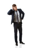 Annoyed businessman covering his ear. Stock Images