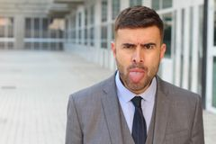 Annoyed businessman sticking his tongue out Stock Photo