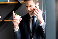 Annoyed businessman is talking on smartphone with wrath Royalty Free Stock Photos
