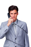 Annoyed businessman tangle up in phone wires Royalty Free Stock Image