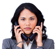 Annoyed businesswoman tangled up in phone wires Stock Images