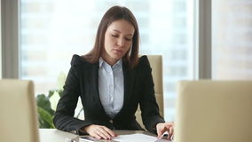 Annoyed businesswoman waiting for clients. Clients are late or didn`t come to meeting. Annoyed businesswoman waiting too long in her office, examining contract stock video footage