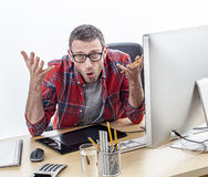 Annoyed casual business man complaining at his desk, expressing misunderstanding. Annoyed casual business man with eyeglasses complaining at his desk, expressing royalty free stock photography