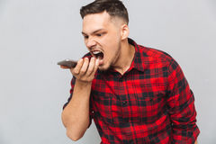 Annoyed casual man in plaid shirt screaming at mobile phone Royalty Free Stock Image