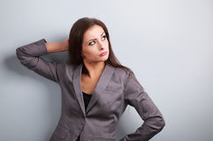 Annoyed concentration business woman in suit looking up on blue Stock Photography