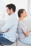 Annoyed couple sitting back to back on the couch Stock Photos