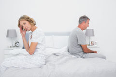 Annoyed couple sitting on different sides of bed having a disput Stock Photo