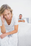 Annoyed couple sitting on opposite ends of bed after a fight. In bedroom at home stock image