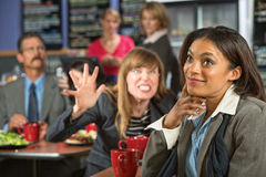 Annoyed Coworker. Behind smiling business women in cafeteria Royalty Free Stock Photography