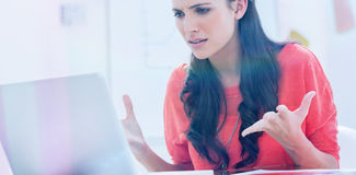 Annoyed designer gesturing in front of her laptop Royalty Free Stock Photos