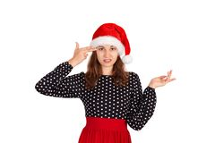 Annoyed and displeased woman in dress shrugging and holding fingers on temple. emotional girl in santa claus christmas hat isolate royalty free stock images