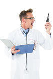 Annoyed doctor with clipboard shouting into a wireless radio Stock Images