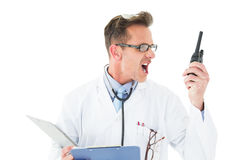 Annoyed doctor with clipboard shouting into a wireless radio Stock Image