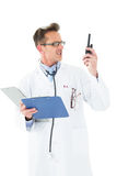 Annoyed doctor with clipboard talking on wireless radio Stock Photos