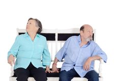 Annoyed eldery couple ignoring each other. And sitting back to back on sofa. Having an argument. Isolated white background Stock Image