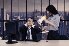 Annoyed employee with her manager near the window Stock Image