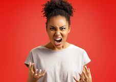 Annoyed girl gestures and shouts in anger. Photo of african american girl wears casual outfit on red background. Emotions and pleasant feelings concept stock photography