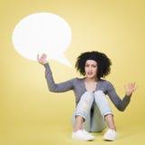 Annoyed girl holding white speech balloon with copyspace. Stock Photos