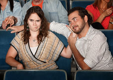 Annoyed Girlfriend In Theater. Girlfriend annoyed with rude men in theater royalty free stock image