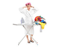 Annoyed housewife with ironing board and clothes Stock Photography