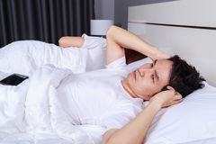 Annoyed husband blocking his ears from noise of wife snoring in. The bedroom Royalty Free Stock Images
