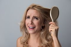 Annoyed lady is holding hairbrush stock image