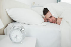 Annoyed Man Being Awakened By An Alarm Clock Stock Photography