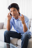 Annoyed man sitting on couch talking on phone Stock Photos