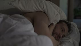 Annoyed man tossing and turning in bed unable to fall asleep, noisy neighbors. Stock footage stock video
