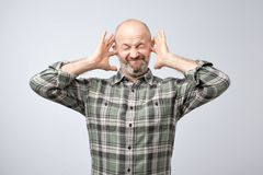 Annoyed mature man plugging ears with fingers stock photography