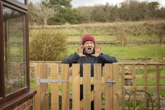 Annoyed mature woman shouting over fence. Outdoors stock image