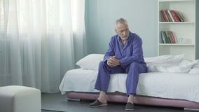 Annoyed old man sitting on bed after awakening, having bad mood in morning. Stock footage stock footage