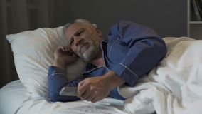 Annoyed pensioner suffering insomnia and nervously switching TV channels. Stock footage Royalty Free Stock Images