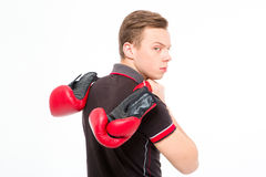 Annoyed sad blond young male carrying boxing gloves Royalty Free Stock Photography