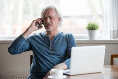 Annoyed aged man having unpleasant phone talk. Annoyed senior man argue over phone explaining his point of view to another person, serious aged male bothered by royalty free stock image